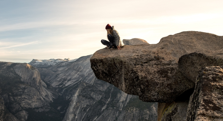 An image of a girl sitting at the edge of a cliff, staring into the valley below. Photo by Casey Horner of Unsplash.