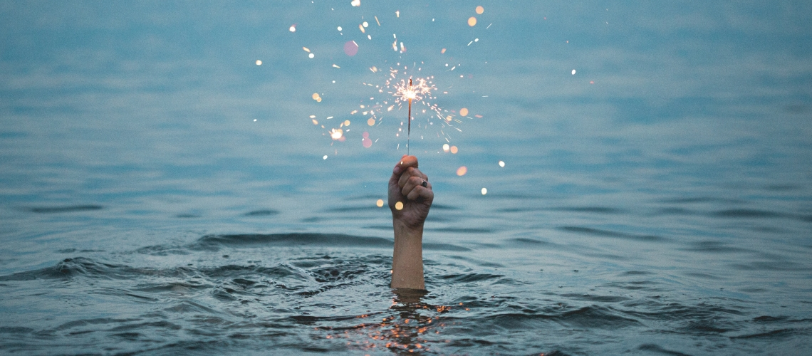 A hand, emerging from a body of water, clutching a lit sparkler.